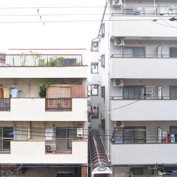 向かいのマンションのベランダが見えます。