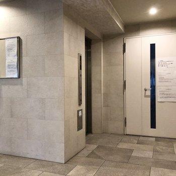 1階の廊下へ続く扉とエレベーター。
