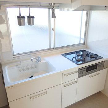 キッチンは3口ガスコンロ付きのシステムキッチン。人造大理石天板の豪華仕様です