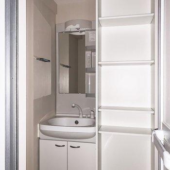 洗面台の横には使い勝手の良さそうな収納棚が。※写真は通電前・フラッシュで撮影しています