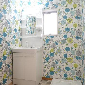 なんだか賑やかな壁紙の脱衣所!入って正面に新しい洗面台と洗濯パン。右手がお風呂です。