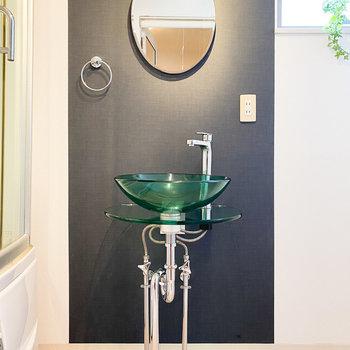 ミニマルで透き通ったデザインの洗面器。丸い鏡も可愛らしい。
