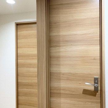 手前はトイレのドア、奥はサニタリーの引き戸。左の空間は…