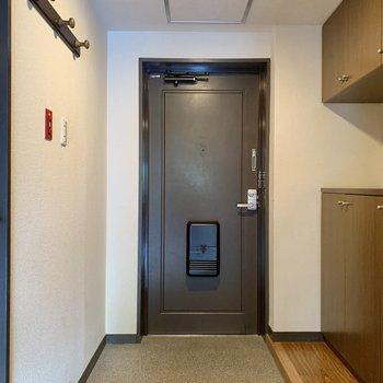 フラットで広めの玄関。木目のハンガーラックもかわいい。
