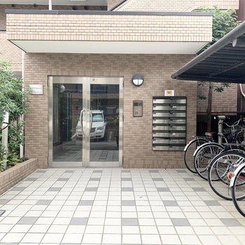 アプローチ右側に自転車置場。オートロック付きマンションです。