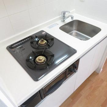 キッチンは2口コンロのシステムキッチン。※写真は10階同間取り・別部屋のものです。