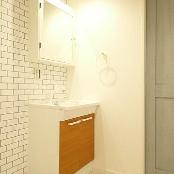 鏡の裏は収納に。レンガ調の壁や扉がかわいいですね。※写真は1階同間取り・別部屋のものです。