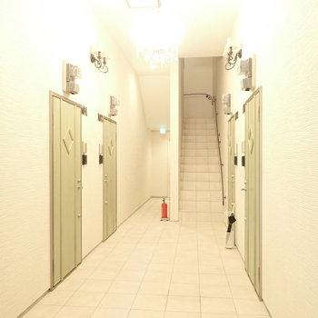 一階の共用部。扉はグリーンです。※写真は1階同間取り・別部屋のものです。