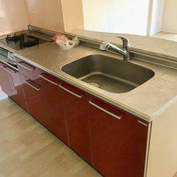 キッチンはぱっと目につく赤。(※写真は1階の同間取り別部屋、清掃前のものです)