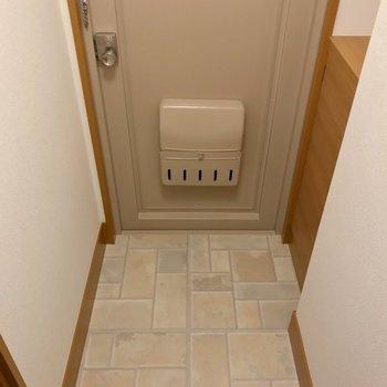 玄関扉とたたきはクリーム色でナチュラル。