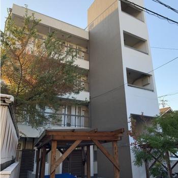 ウッドデッキのアプローチに植木が並ぶ綺麗なマンションに蘇りました。