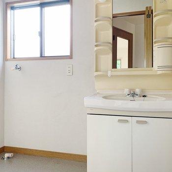 独立洗面台のお隣に洗濯機置き場。小窓つきで明るいですね。