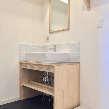 脱衣所。洗面台はタイルと木材でナチュラルです。