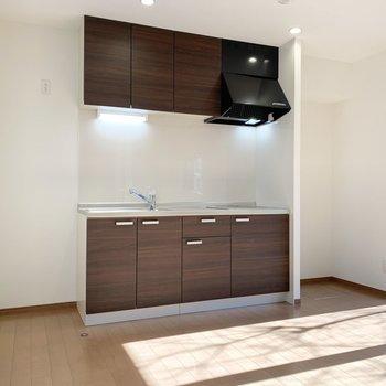 ブラウン調のキッチンに冷蔵庫はお隣へ。