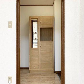 玄関はキッチンの真向かいに。建具はなく、カーテンレールが設置されています。