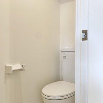 その向かいがトイレです。頭上には棚とブレーカー。