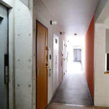 共用部。コンクリとオレンジの壁が特徴的。