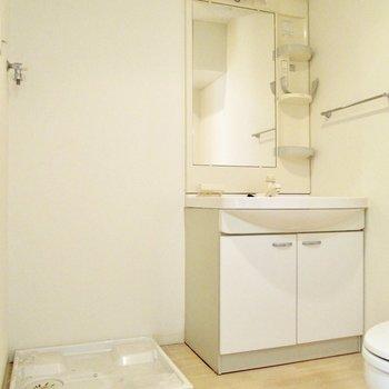 脱衣所に洗面台と洗濯機置き場も。※写真は8階の反転間取り別部屋のものです