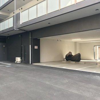 【共用部】マンションの裏手。駐車場とバイク置き場がつながっています。