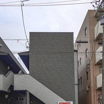 箱のような形の建物。左側には同じ形の建物がもう一つありますが、こちらがお部屋ですよ。