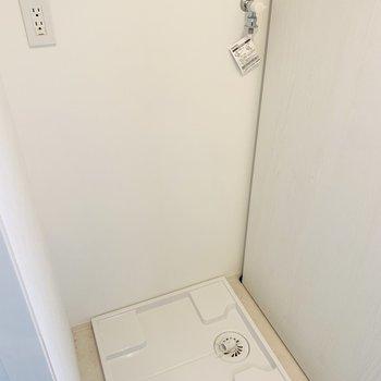 洗面所の正面には洗濯機置き場が。上部には収納も。
