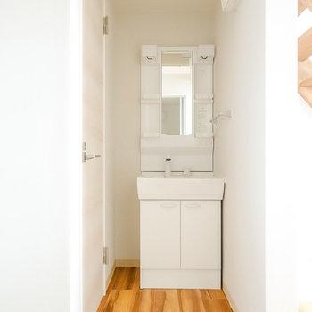 右手には洗面台。棚付きで収納場所にも困らない。
