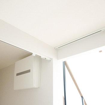 洗面台スペースと玄関は仕切りカーテンで空間を分けることもできる仕様。(※写真は反転間取り別部屋のものです。)