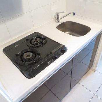 キッチンは黒と白を基調としています※写真は12階別部屋・反転間取りのものです。