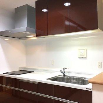 キッチンはワインレッド色。(※写真は6階の同間取り別部屋のものです)