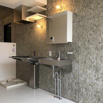 こちら側、とてもスタイリッシュなコンクリ壁をバックに洗面、キッチン、洗濯機が並びます。※写真は3階の同間取り別部屋のものです