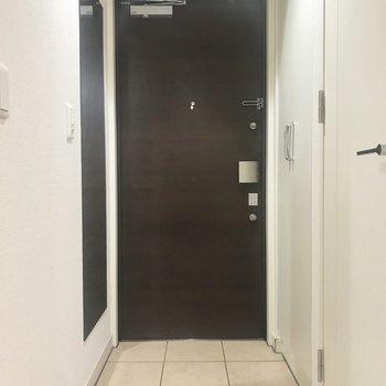玄関。シューズボックスの向かいに姿見があります。