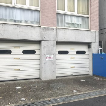 【共用部】入り口に駐車場。右の青いとびらがゴミ置き場です。