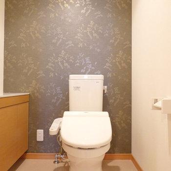 トイレは玄関側の廊下に。アクセントクロスがシックなウォシュレット付き。