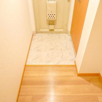 洋室を出て正面に玄関。土間は大理石調で高級感アリ。
