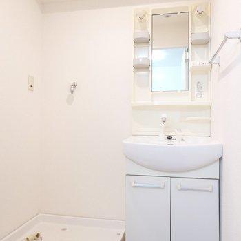棚付きの洗面台とその隣に洗濯機置き場。