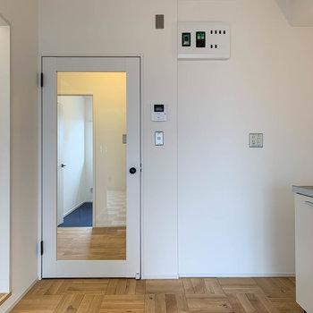【LDK】キッチンの左、クリアな扉を開けると玄関前のホールへ。