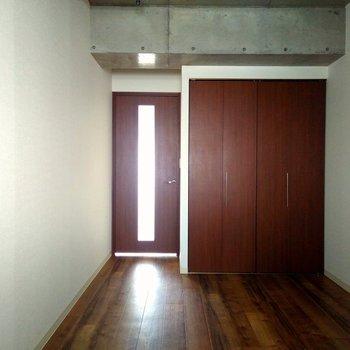 コンクリと白い壁のクロス、茶色のドアとクローゼットのコントラストが良い