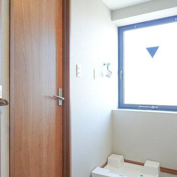 窓があり明るい脱衣所。正面には洗濯パンと、左にはトイレ。