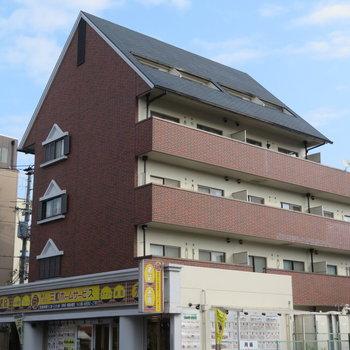 三角形の屋根が特徴のブラウンのマンション
