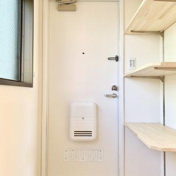 白の玄関に無垢のオープン棚がよく似合います。