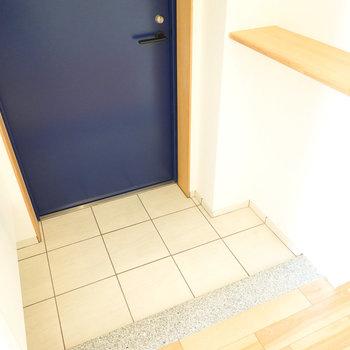 四角いタイル床の少し広めの玄関。鍵などの一時置きに便利な小物棚も。