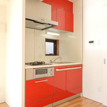 情熱的な赤が映えるキッチン。冷蔵庫置き場は背面側に。