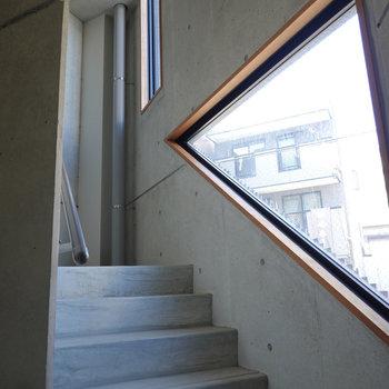 コンクリの風合いがクールな、窓のある共用階段。