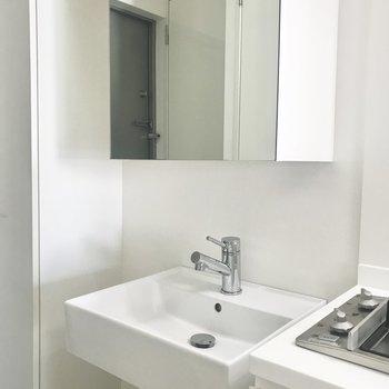 キッチン左隣に洗面台があります。鏡の奥は収納スペースでした。コンセントもあります。