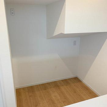 【LDK】後ろに冷蔵庫置き場。階段下あたりなので段々になっています。