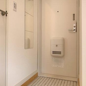 玄関には白いタイルを敷き詰めて。
