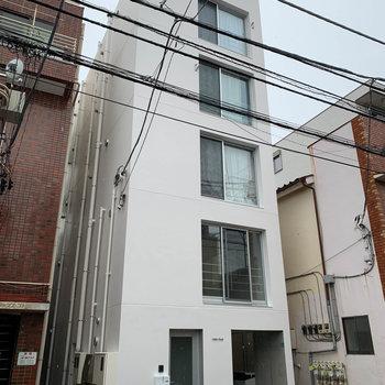 白い縦長のマンション