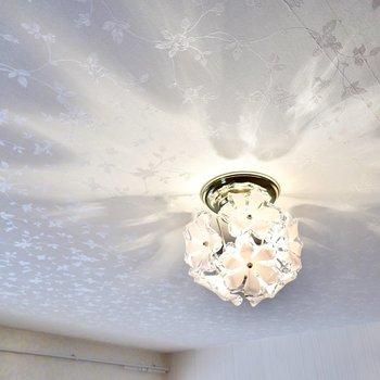 花の形のペンダントライトが可愛い。天井には壁とは違う柄の花模様のクロスが貼られています。