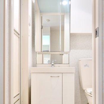キッチンの背面側には脱衣所。ドアを開けると、ホテルライクな洗面台が…!