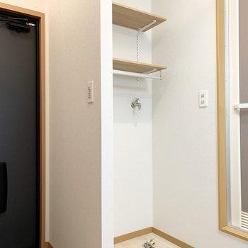 キッチンの後ろを振り返ると水廻り。まず左側に棚付の洗濯機置場。